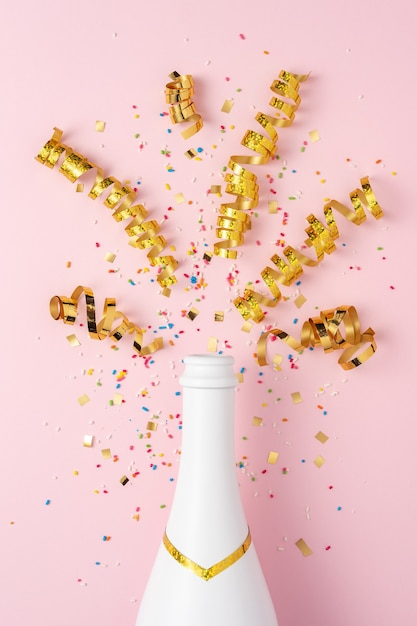 ピンクの背景に紙吹雪とパーティーストリーマーと白いシャンパンボトル。 Premium写真