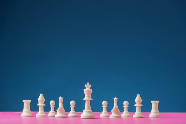 キングピースをリードにしたピンクのボードに配置された白いチェスフィギュア Premium写真
