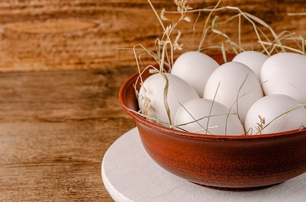 Белые куриные яйца в миске на деревенском деревянном столе Premium Фотографии