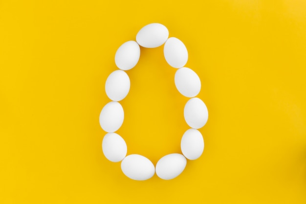 White chicken eggs lie in the shape of a big egg on yellow Premium Photo
