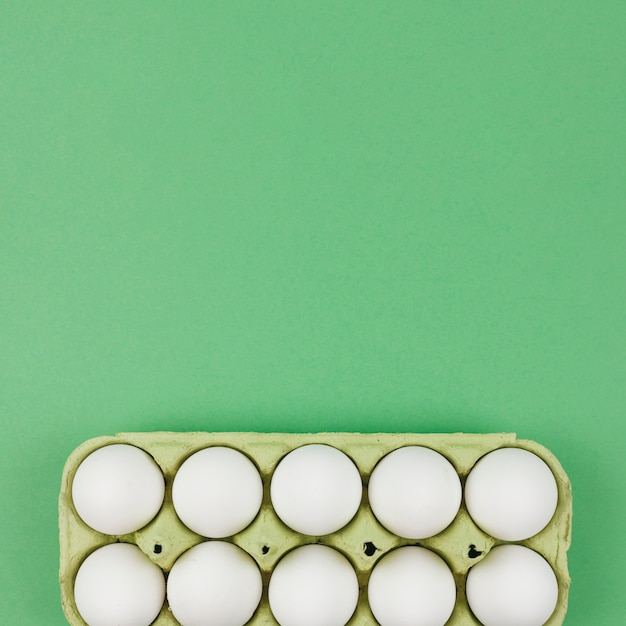 White chicken eggs in rack on green table Free Photo