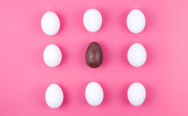 White chicken eggs with chocolate egg on table Free Photo