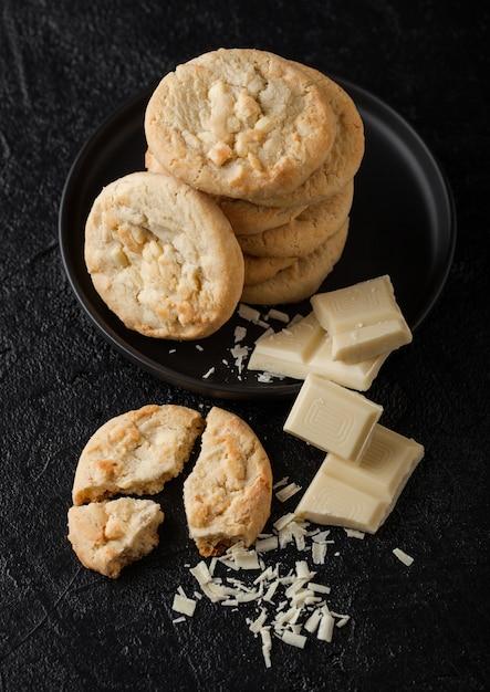 チョコレートブロックと暗いテーブルのカールと黒のセラミックプレートにホワイトチョコレートビスケットクッキー。 Premium写真