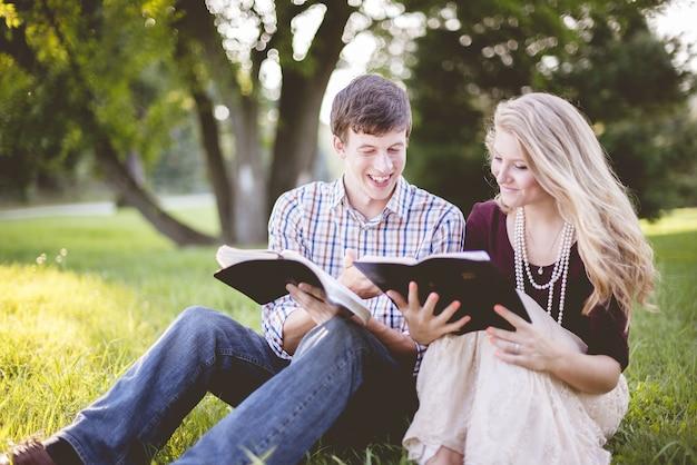 フィールドの真ん中で聖書を読んで楽しんでいる白人のキリスト教徒のカップル 無料写真
