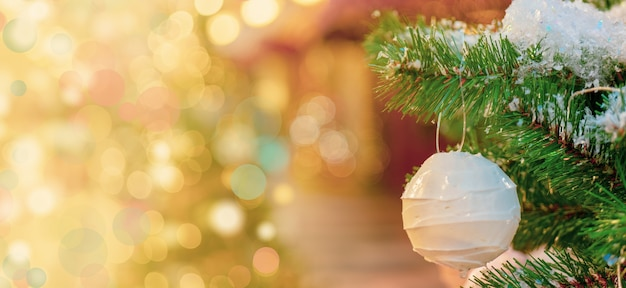 White christmas ball hanging on a snowy fir tree branch, bokeh effect background Free Photo