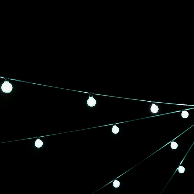 White christmas incandescent light bulb decoration against black backdrop Free Photo