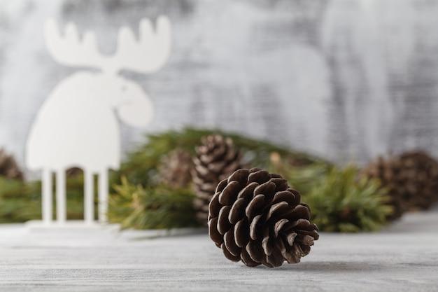 ホワイトクリスマスの飾り、素朴な木のテーブルにクリスマスツリー。メリークリスマスカード。冬の休日のテーマ。明けましておめでとうございます。 Premium写真