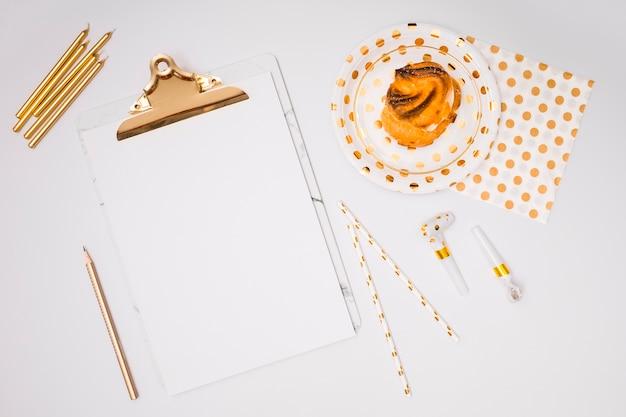White clipboard mock-up next to yellow birthday supplies Free Photo