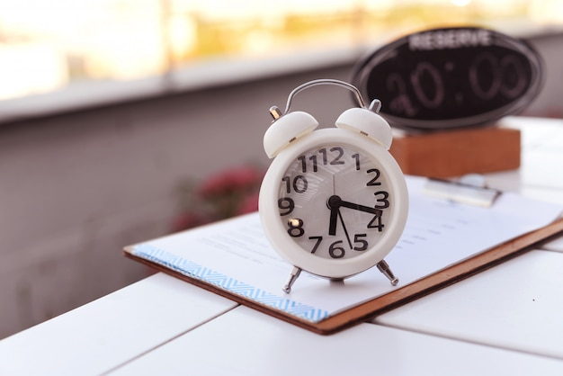 White clock alarm with a turntable on the table outside in a restaurant Premium Photo