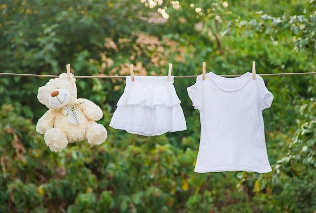 夏には白い服がロープで乾きます。 Premium写真
