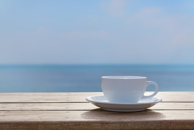 White coffe cup on wood table top with blurred sea sky background Premium Photo