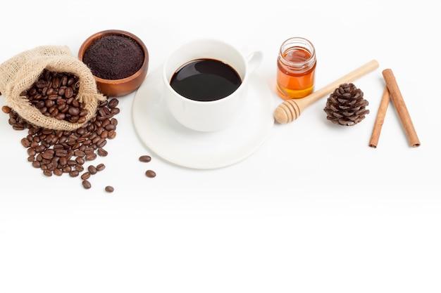 White coffee cup and  fresh coffee beans honey sugar on wood spoon white Premium Photo