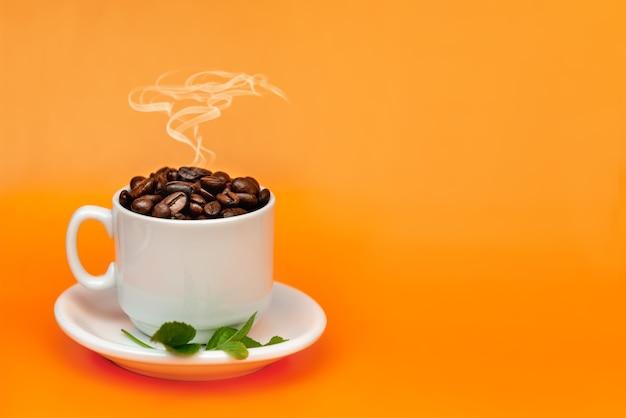 上に煙が付いているオレンジ色の背景にコーヒー豆でいっぱいの白いコーヒーカップ。国際コーヒーの日のコンセプト。 Premium写真