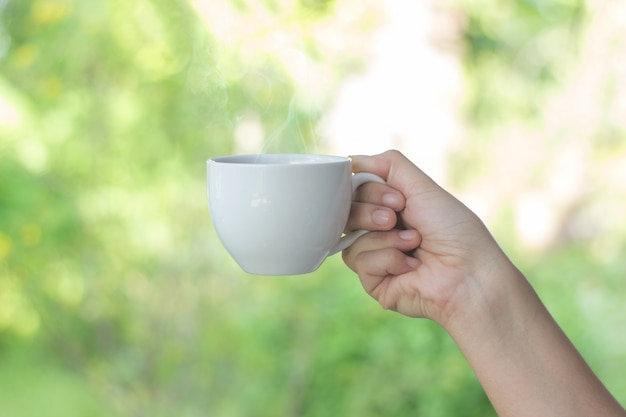 White coffee cup in hand blur background,young women drinking coffee Premium Photo