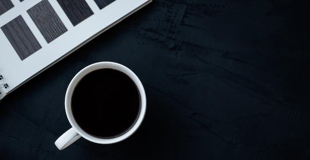 黒いテーブルの上の白いコーヒーカップ Premium写真