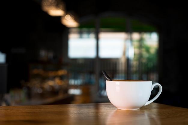 コーヒーショップで木製の机の上の白いコーヒーカップ Premium写真