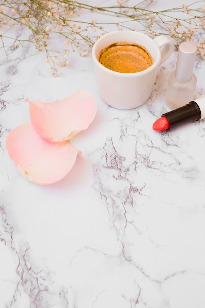 White coffee cup; rose petals; nail polish bottle; baby's-breath flowers and lipstick on white textured backdrop Free Photo