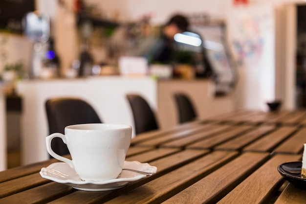 White coffee cup and saucer over the wooden table in the coffee bar Free Photo