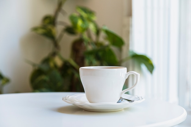 White coffee cup and spoon on ceramic saucer over white table Free Photo