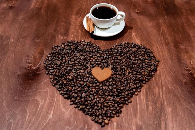Кружка белого кофе, пряники и кофейные зерна на деревянной доске Premium Фотографии