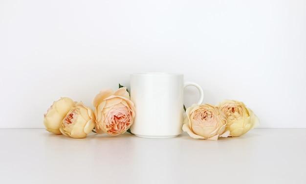 White coffee mug  with roses. blank mug mock up for design promotion. Premium Photo