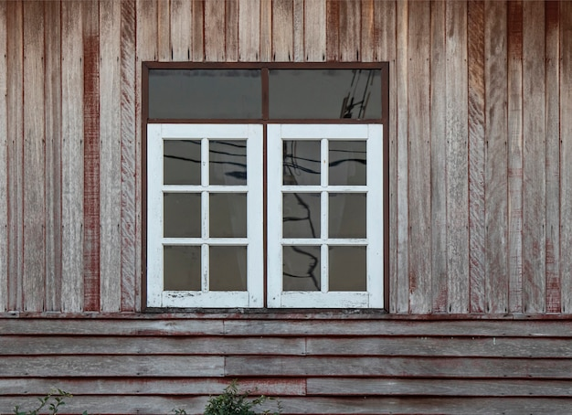White color windows and old brown wooden wall. Premium Photo