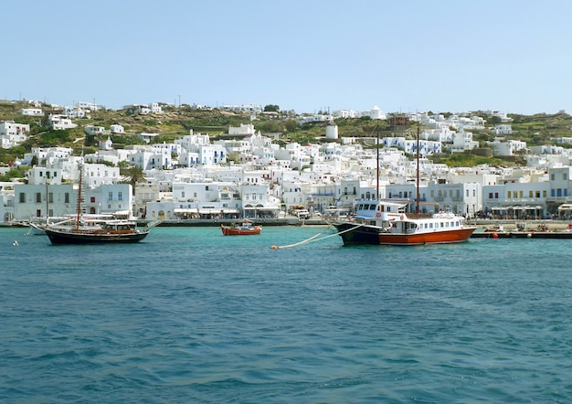 White colored greek islands architecture on the hillside with boats at mykonos old port, greece Premium Photo