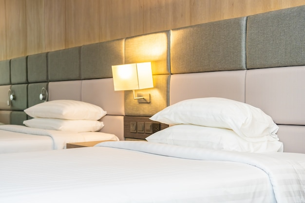 Белая удобная подушка и одеяло на кровати с легкой лампой Бесплатные Фотографии