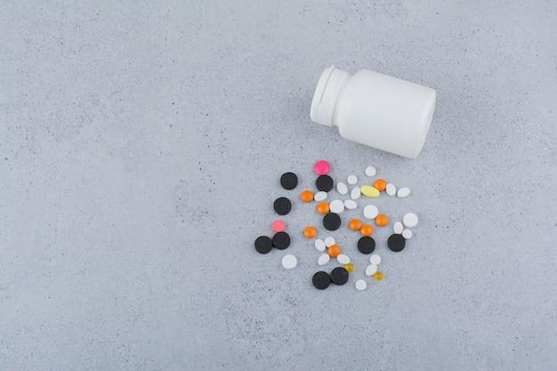 Contenitore bianco e mazzo di varie pillole sulla superficie di marmo. Foto Gratuite