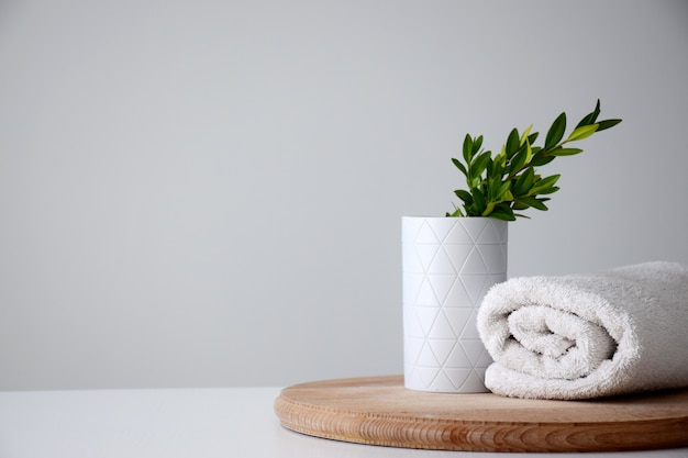 White container with green herb and white rolled towel on wooden board Premium Photo