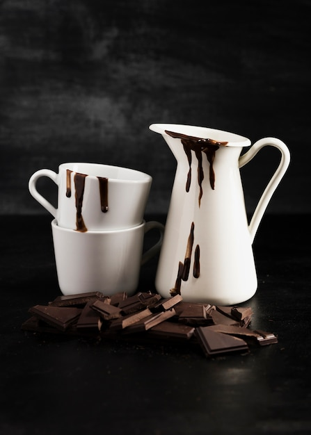White containers filled with melted chocolate and pieces of chocolate Free Photo