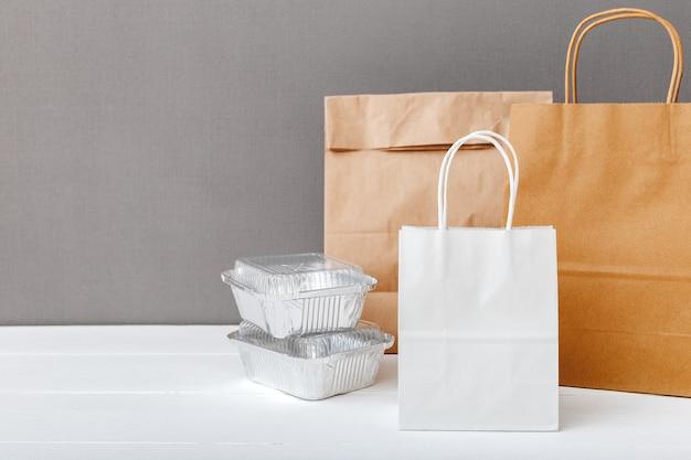 Белые бумажные пакеты и контейнеры для пищевых продуктов на белом столе сером фоне. служба доставки еды. Premium Фотографии