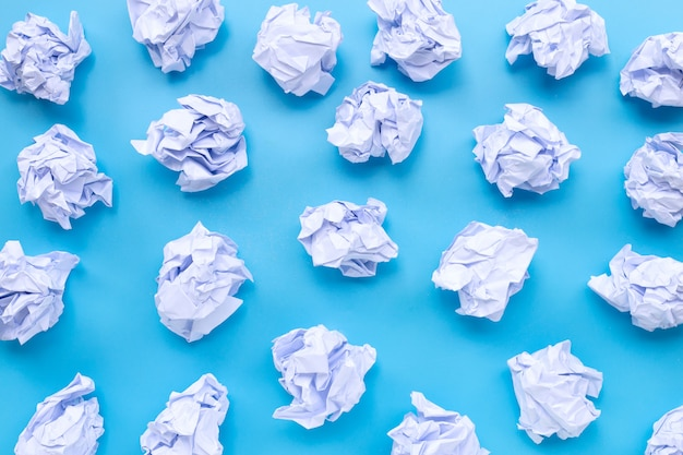 White crumpled paper balls on a blue background. Premium Photo