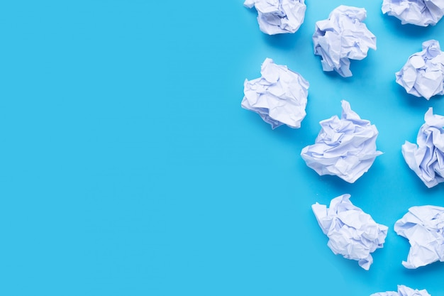 White crumpled paper balls on a blue background. Premium Photo