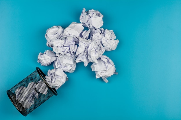 White crumpled paper balls rolling out of a black trash can on blue background. Premium Photo