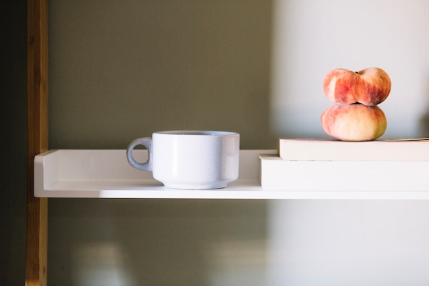 White cup and peaches Free Photo