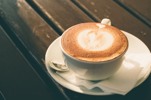 White cup of cappuccino with cinnamon on a wooden table in a cafe Premium Photo