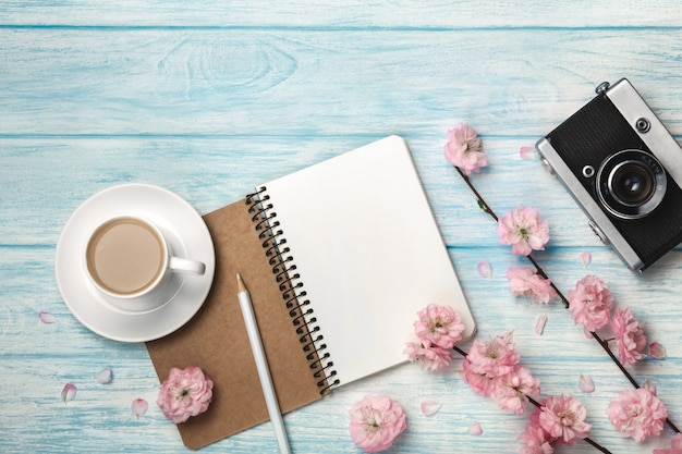White cup cappuccino with sakura flowers, notebook and old photo camera on a blue wooden table Premium Photo