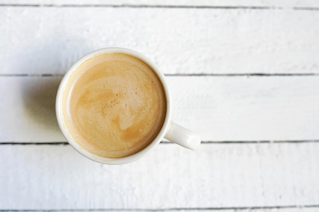 White cup of coffe , copy space on white wooden Premium Photo
