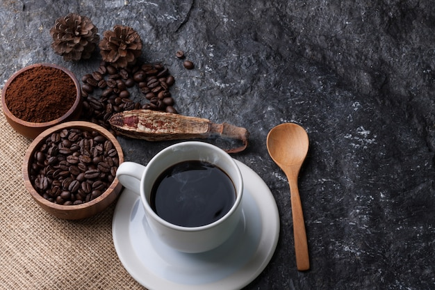 White cup coffee , coffee beans in wooden cup on burlap , wood spoon  on black stone  background Premium Photo
