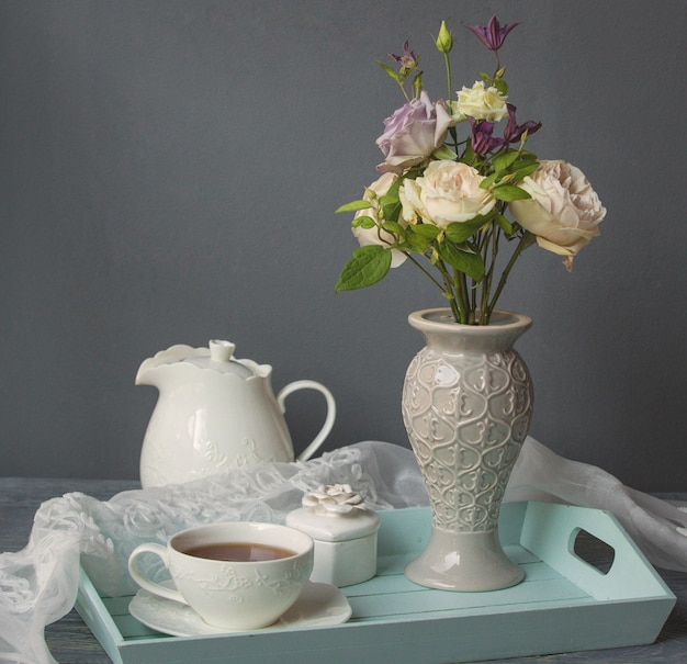 A white cup of coffee, kettle and vase of flowers Free Photo