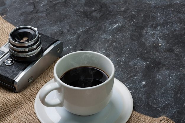 White cup coffee and old camera on burlap in black stone Premium Photo