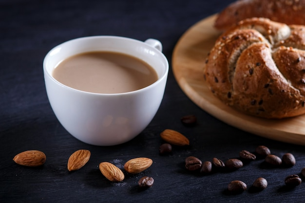 White cup of coffee with cream  and buns on a black background. Premium Photo