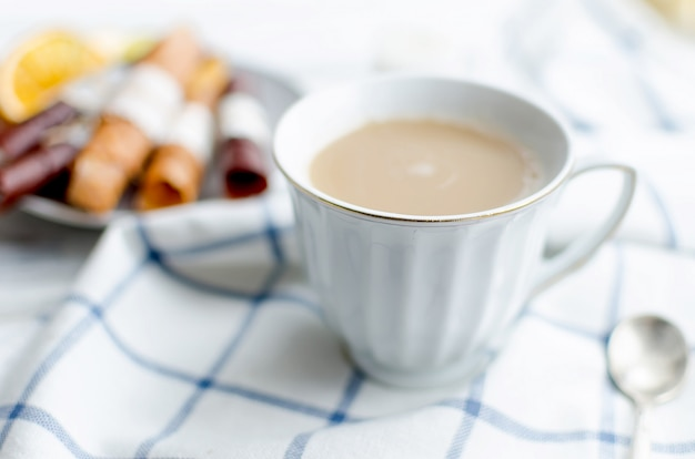 White cup of coffee with milk and fruit pastille and chips Premium Photo
