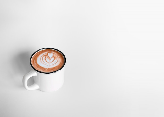 A white cup of hot coffee latte art on white background with copy space. top view Premium Photo