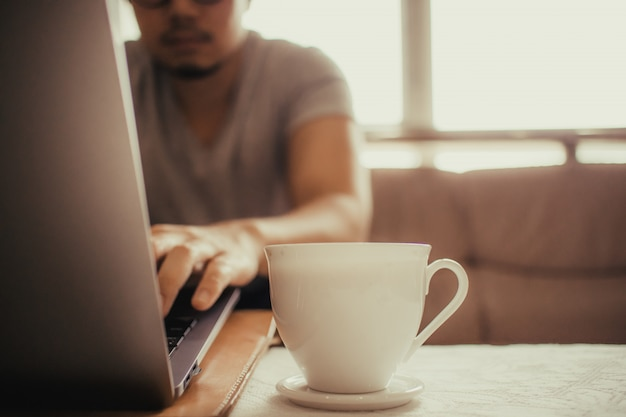 White cup of hot coffee on the table of a freelance man. Premium Photo