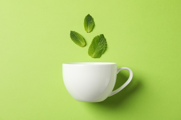 White cup and leaves on green, space for text Premium Photo