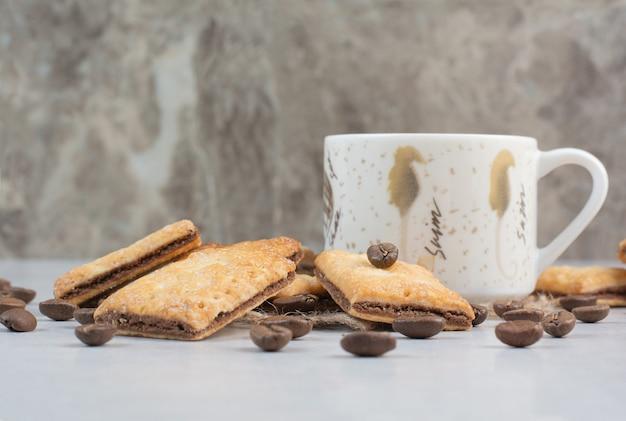 白い背景にクラッカーとコーヒー豆とコーヒーの白いカップ。高品質の写真 無料写真