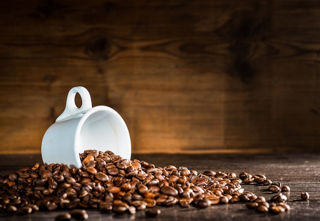 White cup surrounded by coffee beans Free Photo