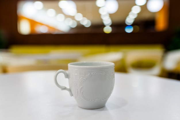 White cup on the white table and a blurred background. Premium Photo